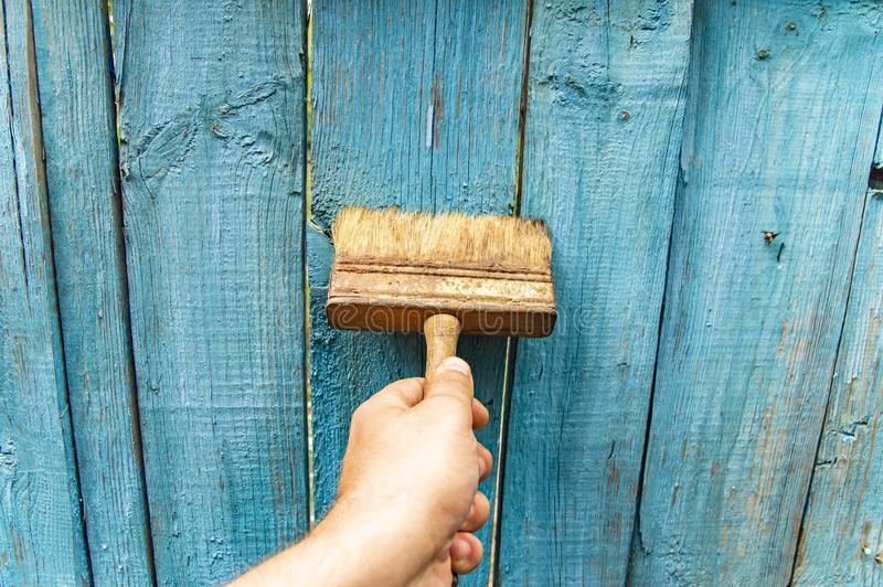 Brush in hand - painting a wooden fence royalty free stock images