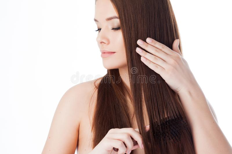 Brush her hair. Attractive girl with long hair. Portrait of a beautiful young woman using a comb royalty free stock photos