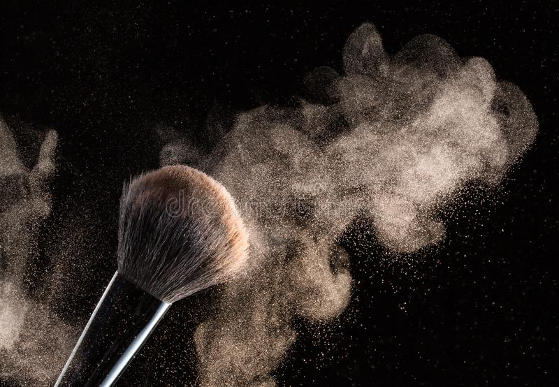 Brush for makeup with flying around powder is isolated on a black background.  royalty free stock image