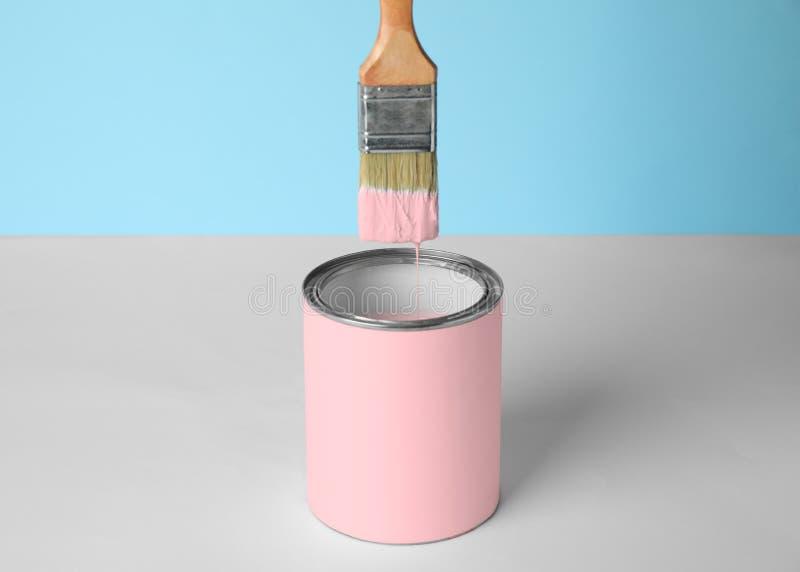 Brush over может розовой краски на таблице против сини стоковое фото rf