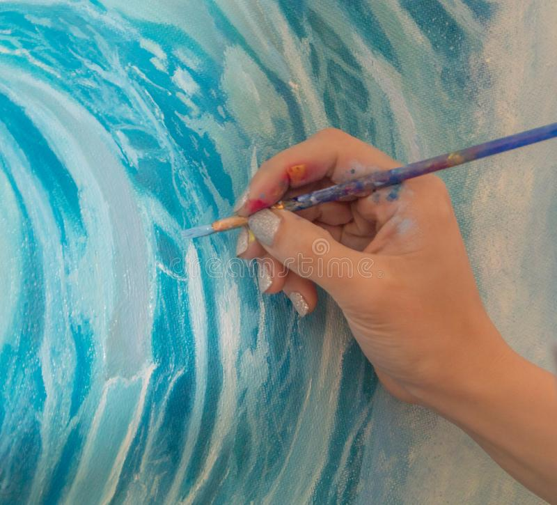 The brush with paint in the artist`s hand. stock photos