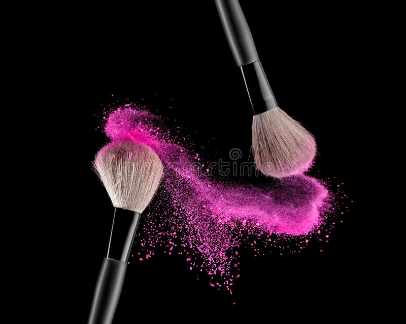 Brush with powder. Make-up brush with pink powder explosion on black background royalty free stock photos