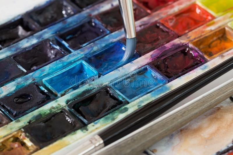Brush and professional colorful watercolor paints closeup stock photography