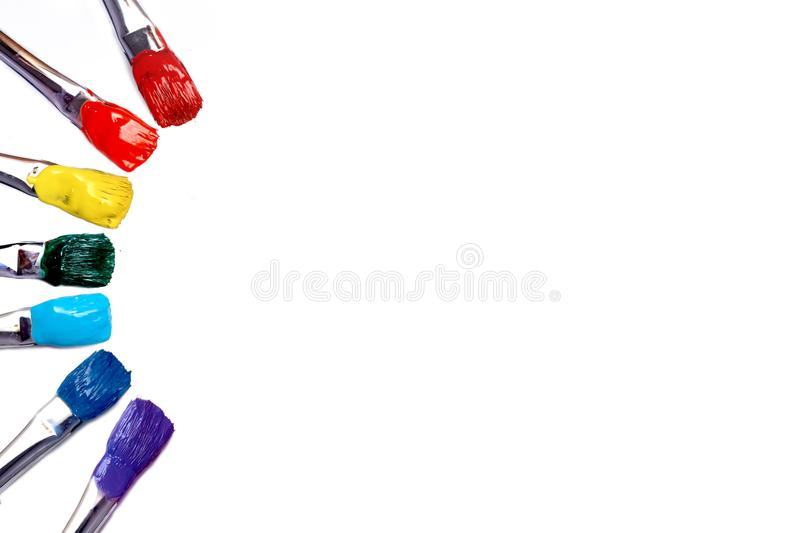 Brush with red, orange, yellow, green, blue, and blue paint. stock photo