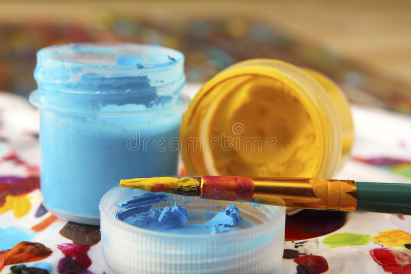 The brush is smeared with yellow paint on the background of colored cans with acrylic paint. Close-up. Sharpness on brush. stock photo