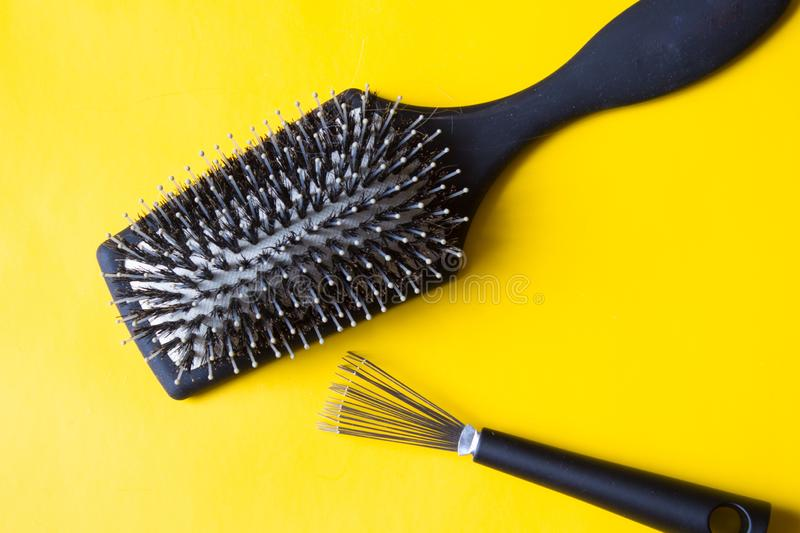 Brush and special tool will help remove tangles and dust stuck between the teeth or bristles. Yellow background. Top view royalty free stock photo