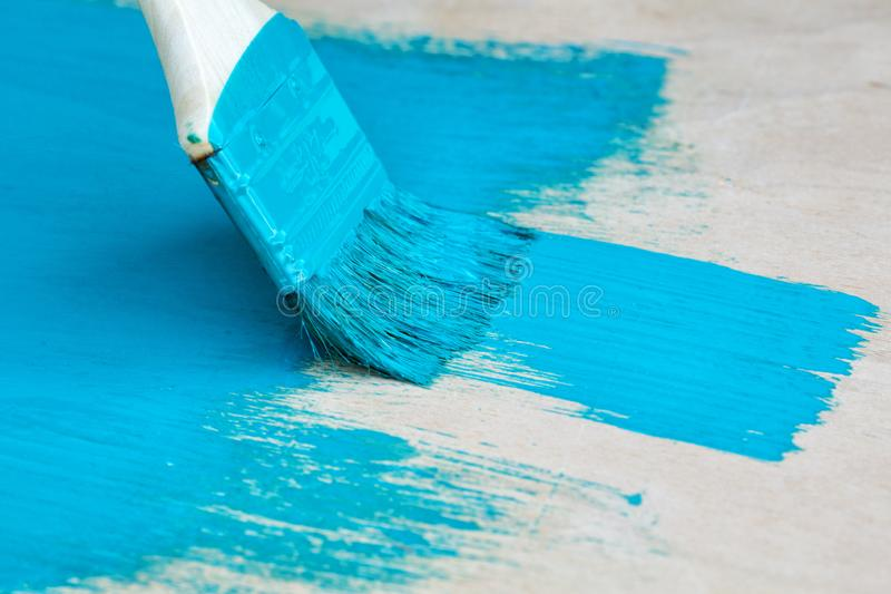 Brush with turquoise paint close-up on a painted. Surface background royalty free stock photography