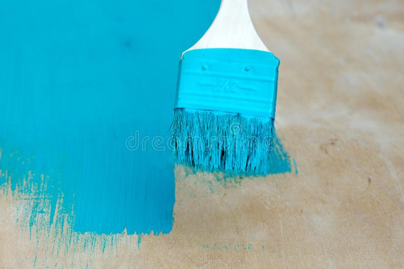 Brush with turquoise paint close-up on a painted. Surface background stock images