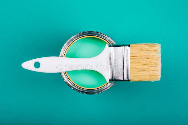 Brush on open can with turquoise color of paint on blue background. Brush with white handle on open can with turquoise color of paint on blue background stock photos