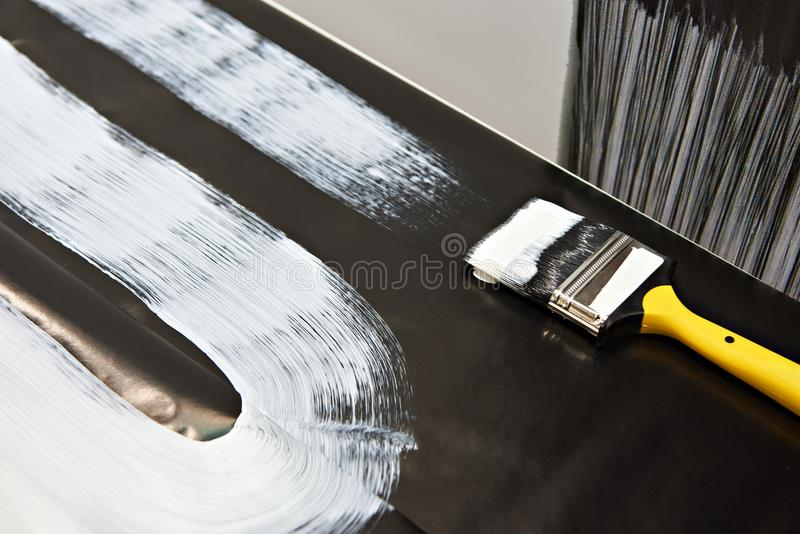 Brush and white paint on black surface royalty free stock photography