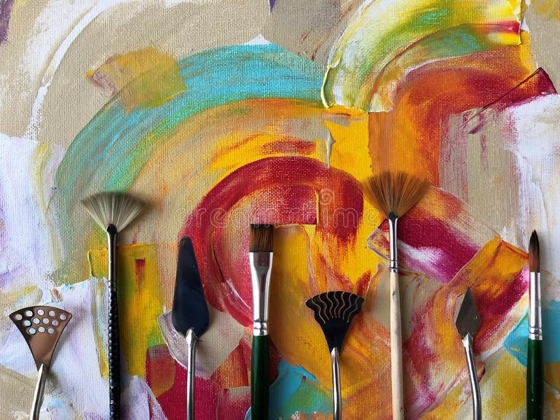 Brushes on abstract acrylic background. Multicolored abstract acrylic background with brushes. Art therapy stock images