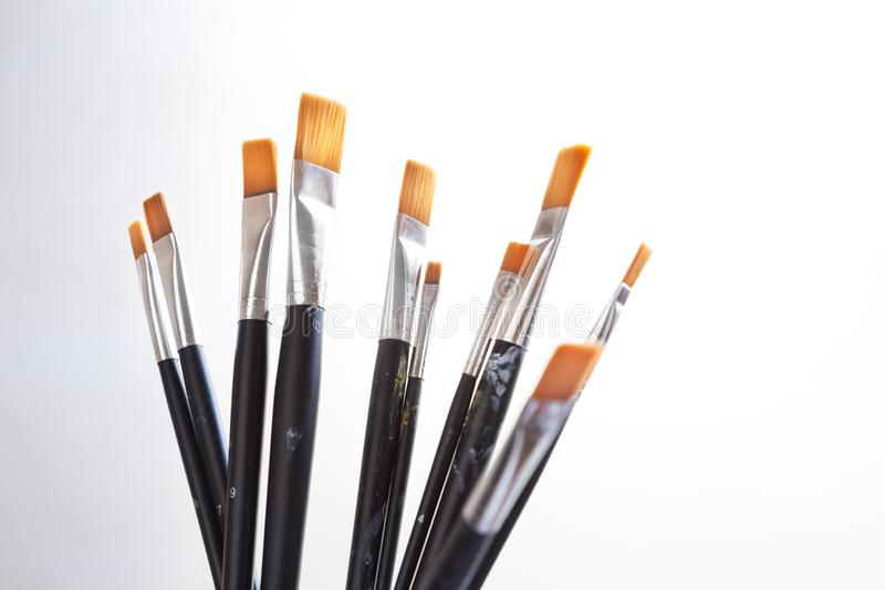 Brushes background on white. Fine art brushes of different sizes standing mixed ready to start a new project on white background, beginning a creative project stock image