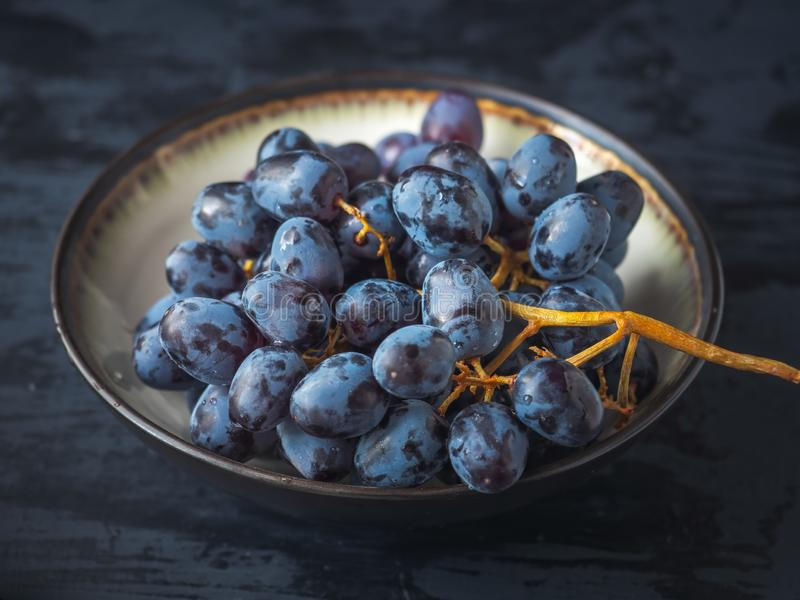 Brushes of black grapes, one in a ceramic plate, the other on a dark table, taken at close range stock photos