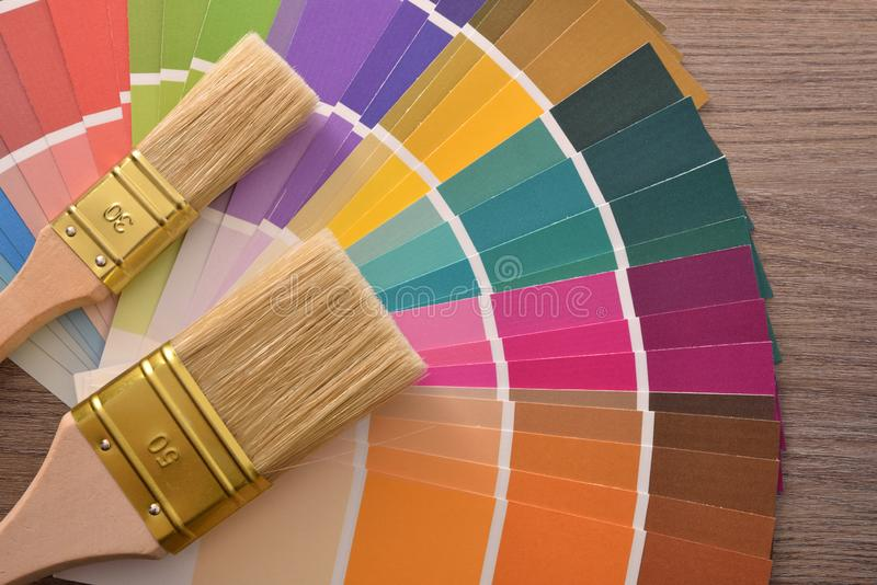 Brushes on color fan chart on a brown wooden table royalty free stock photo