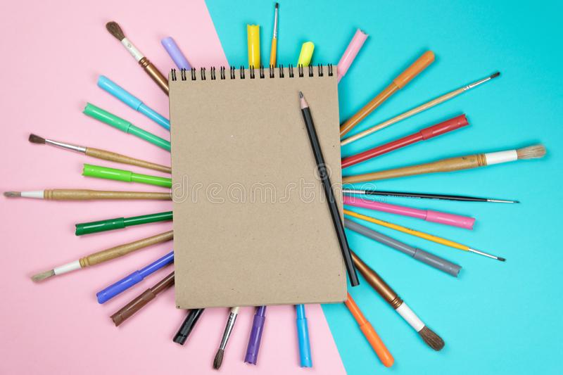 Brushes, colored pencils, notebook mock up for artwork. stock photos