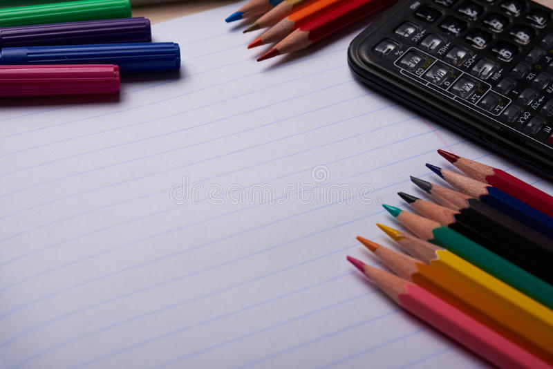 Brushes, colored pencils and other tools. Notebook with school supplies on a wooden background royalty free stock photography
