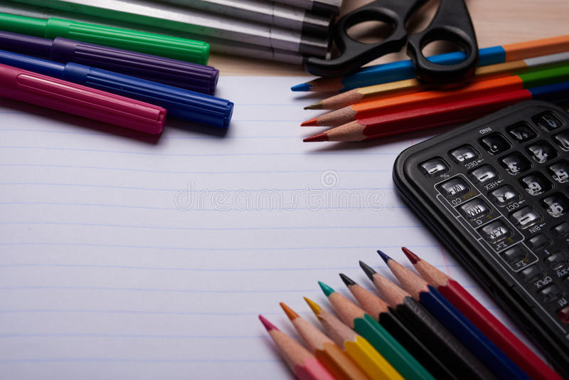 Brushes, colored pencils and other tools. Notebook with school supplies on a wooden background stock images