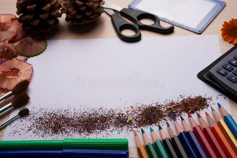 Brushes, colored pencils and other tools. Notebook with school supplies on a wooden background royalty free stock photo