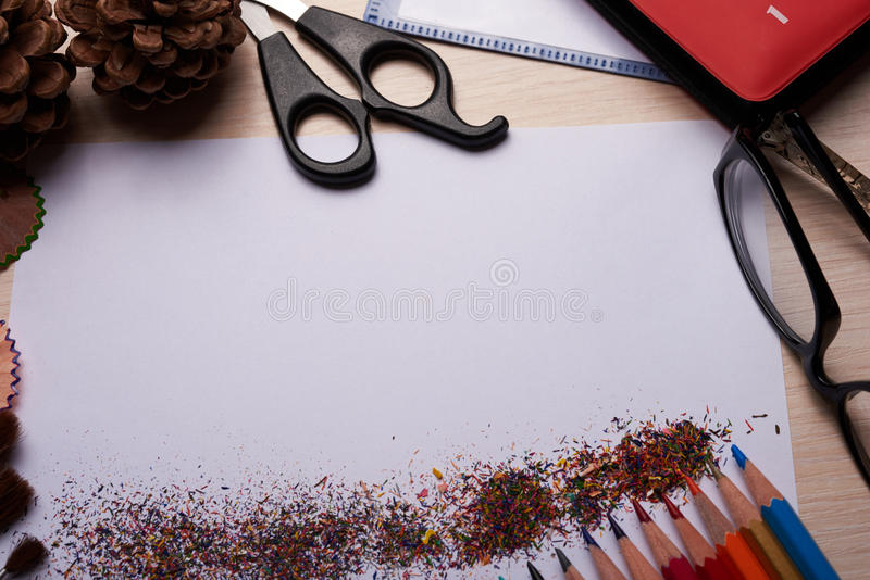Brushes, colored pencils and other tools. Notebook with school supplies on a wooden background stock photography