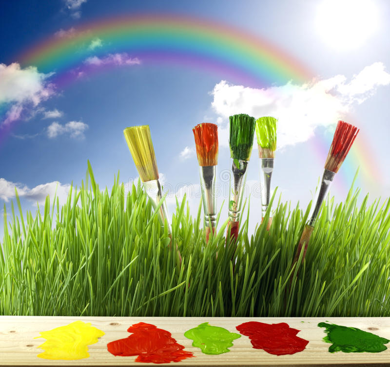 Brushes colors of nature. Colors of nature with green grass and raibow and painting brushes stock image