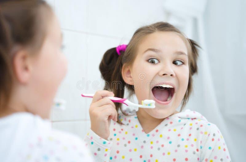 brushes flickan henne tänder royaltyfria bilder