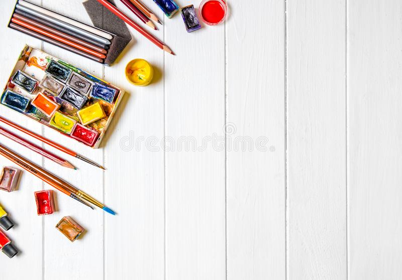 Brushes and paints with pencils on wooden background royalty free stock images