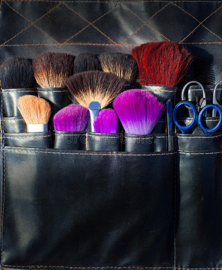 Brushes scissors and tools of makeup artist in black stock image