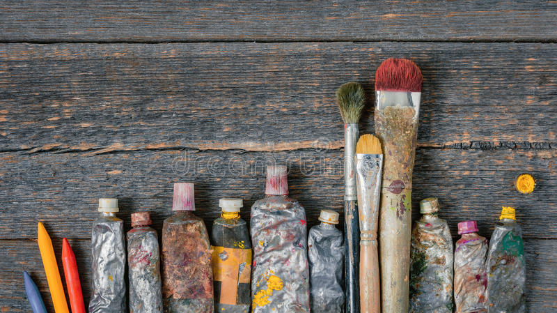 Brushes, tubes with paint and colored pencils stock photos