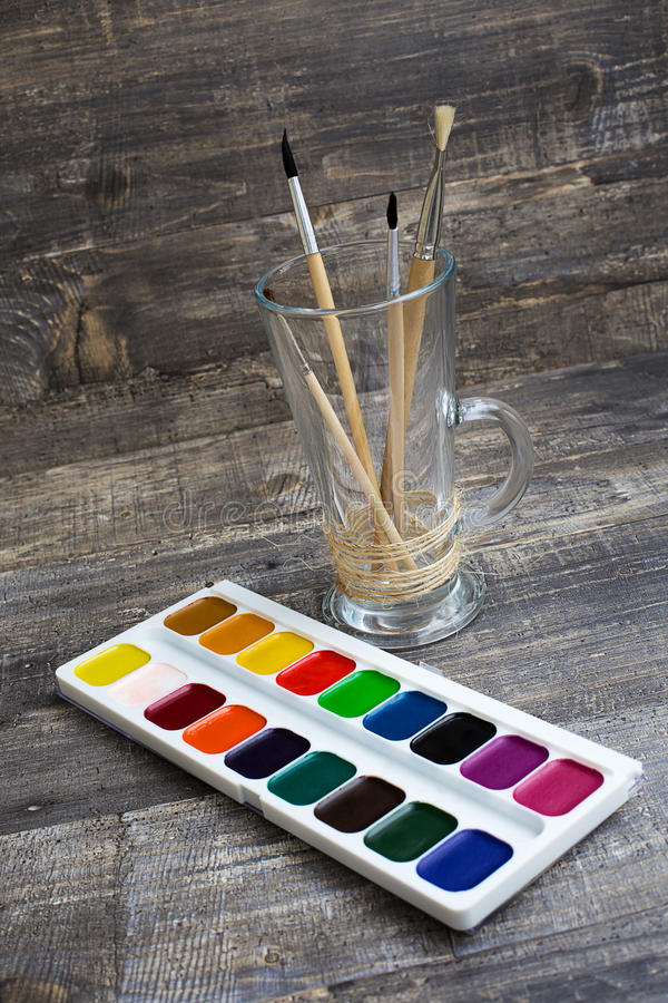 Brushes in vase and watercolor paints. On wooden background. Vertical diagonal imagination stock image