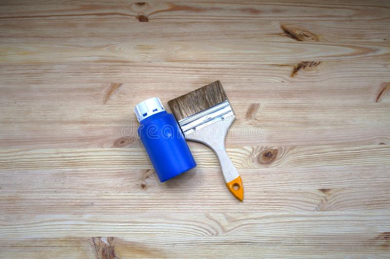 Brushes on wooden floor with jar of paint top view. Blue paint can. Wooden background stock photo