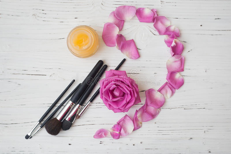 Brushes , yellow cream and pink rose on white wooden table royalty free stock image