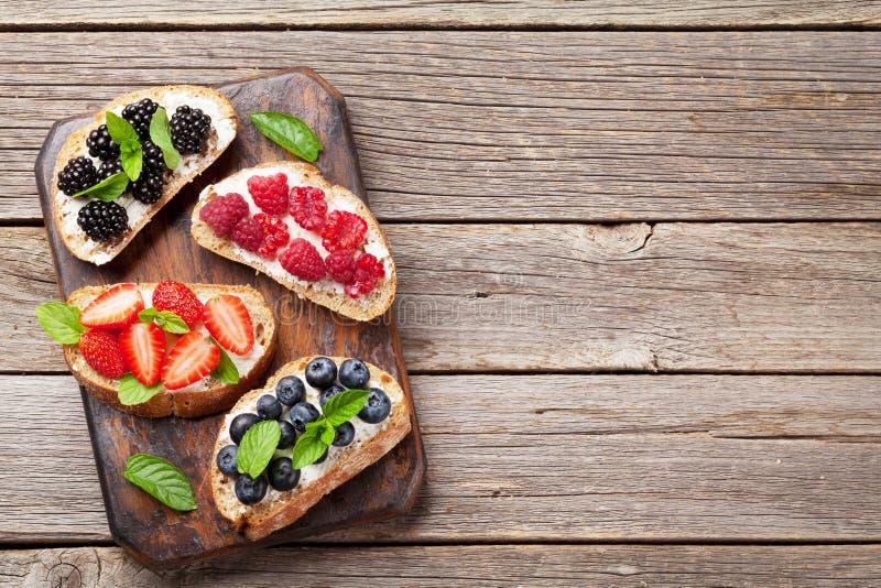 Brushetta或传统西班牙塔帕纤维布用各种各样的莓果 被设置的开胃菜意大利开胃小菜快餐 顶视图和舱内甲板放置与 库存照片