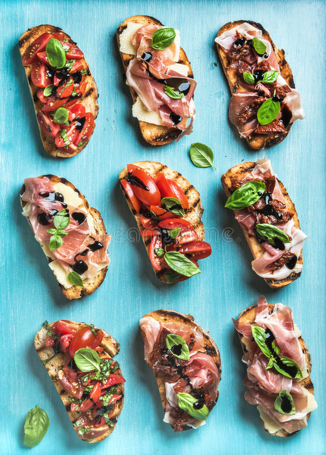 Brushetta установило для вина Разнообразие малых сандвичей на фоне сини бирюзы, взгляд сверху стоковое изображение