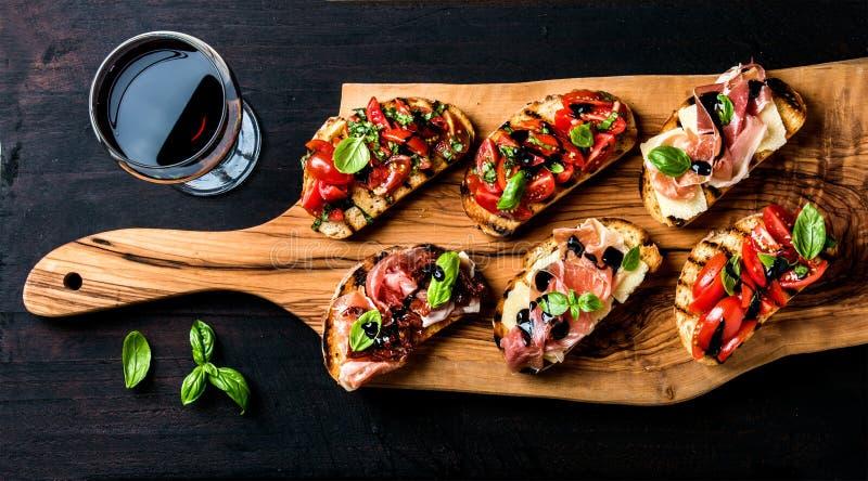 Brushetta ajustou-se e vidro do vinho tinto Sanduíches pequenos com prosciutto, tomates, queijo parmesão, manjericão fresca, bals fotografia de stock