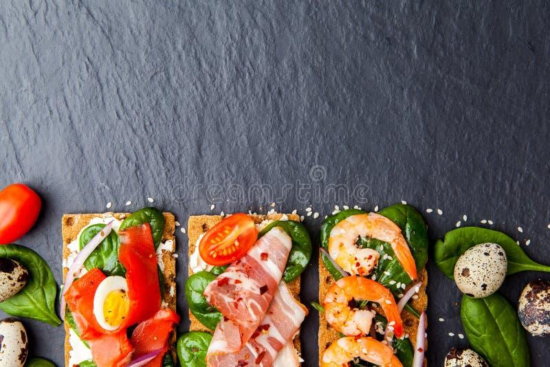 Brushetta ajustou-se no fundo escuro Variedade de sanduíches pequenos d imagem de stock