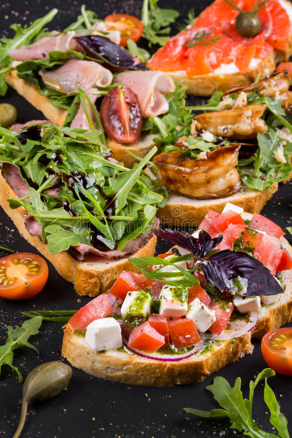 Brushetta ajustou-se para o vinho Variedade de sanduíches pequenos com prosciutto, tomates, queijo parmesão, manjericão fresca fotografia de stock
