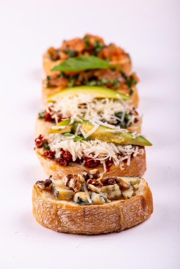 Brushetta ajustou-se para um aperitivo A variedade de sandu?ches pequenos com tomates, queijo parmes?o, abacate e noz serviu sobr fotos de stock