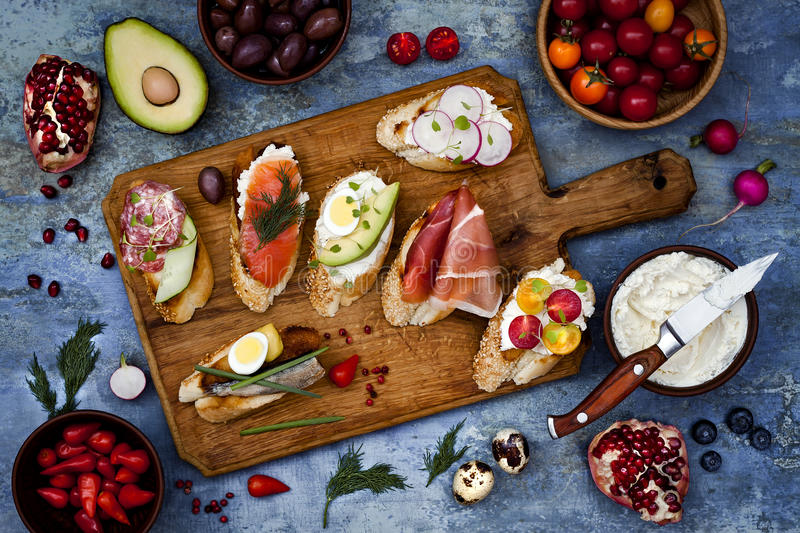 Brushetta or authentic traditional spanish tapas set for lunch table. Sharing antipasti on party picnic time on blue background. Brushetta or authentic stock image
