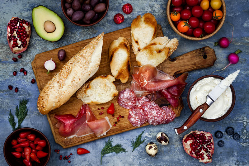 Brushetta or authentic traditional spanish tapas set for lunch table. Sharing antipasti on party picnic time on blue background royalty free stock images