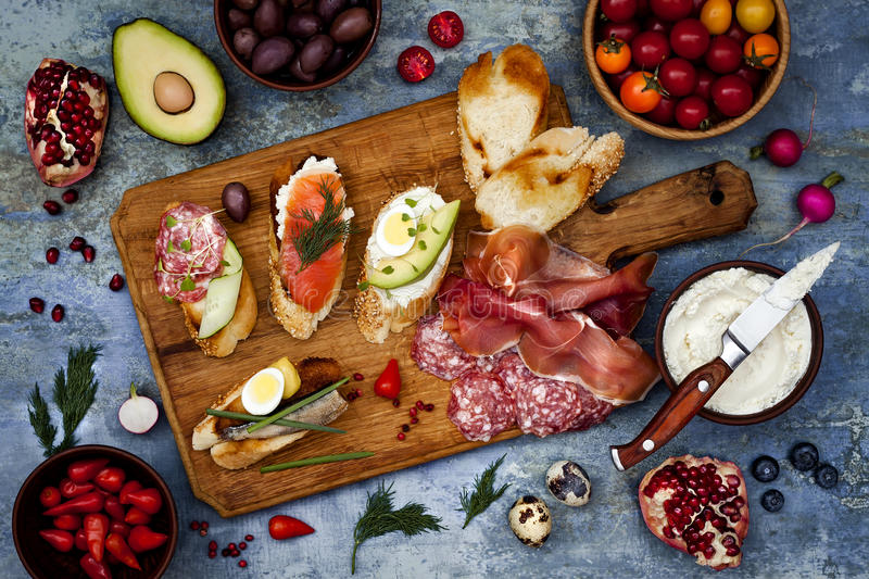 Brushetta or authentic traditional spanish tapas set for lunch table. Sharing antipasti on party picnic time on blue background. Brushetta or authentic royalty free stock photography