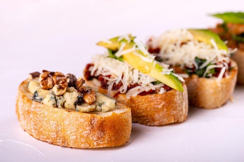 Brushetta ha messo per un aperitivo La varietà di piccoli panini con i pomodori, il parmigiano, l'avocado e la noce è servito sop fotografia stock