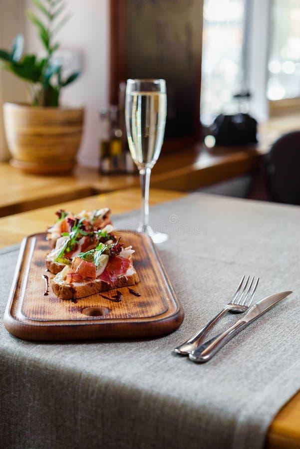 Brushetta ha messo per vino Varietà di piccoli panini con il prosciutto di Parma, i pomodori, il parmigiano, il rucola fresco ed  immagini stock