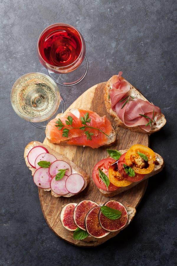 Brushetta lub tradycyjni hiszpańscy tapas Zakąsek antipasti włoskie przekąski ustawiają na drewnianej desce z różanym i białym wi fotografia royalty free
