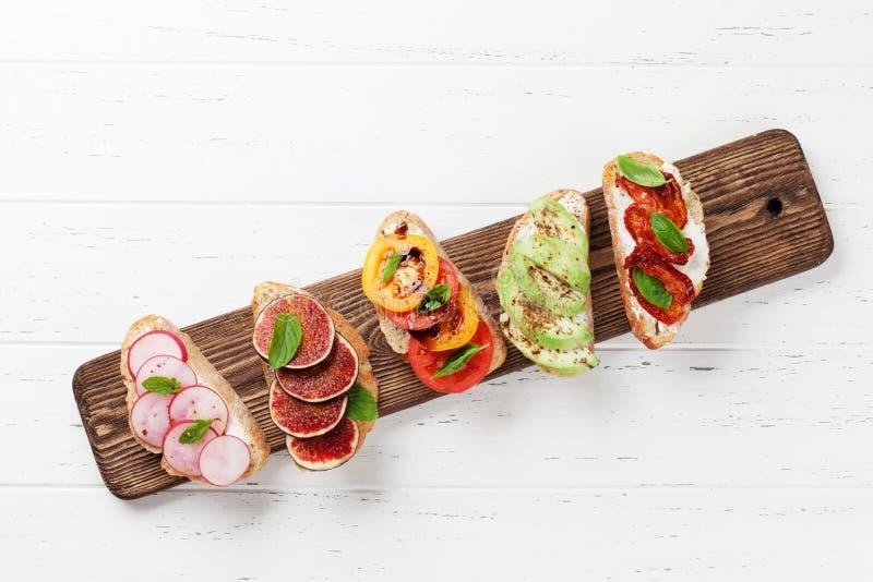Brushetta oder traditionelle spanische Tapas Aperitifs stellten italienische Antipastisnäcke auf hölzernes Brett ein Draufsicht u lizenzfreie stockbilder