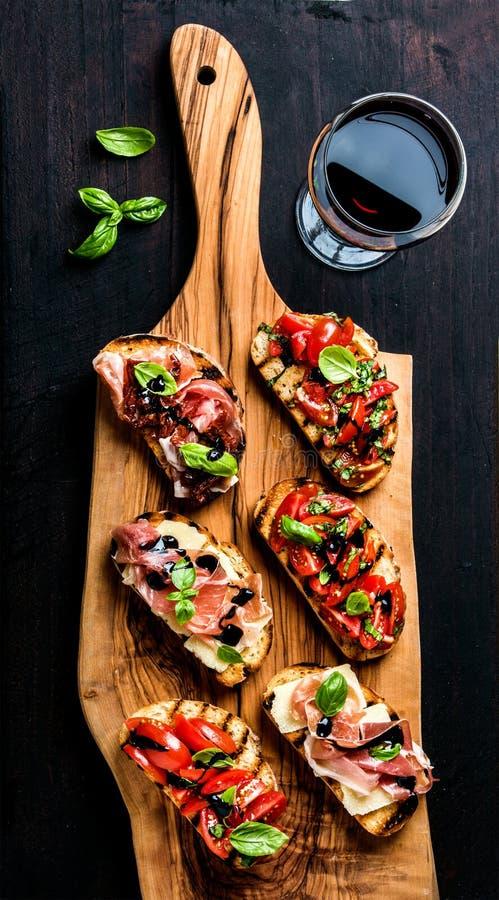 Brushetta ustawia i szkło czerwone wino Małe kanapki z prosciutto, pomidory, parmesan ser, świeży basil, balsamic fotografia stock