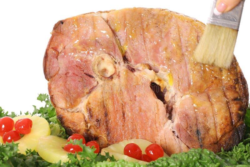 Brushing ham with glaze stock images