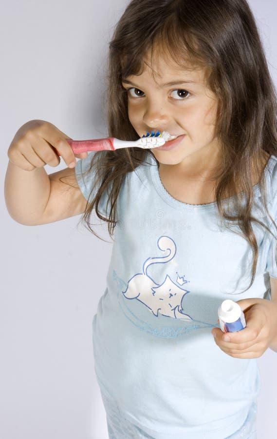 Brusihng teeth. Young girl brusihng her teeth stock photos