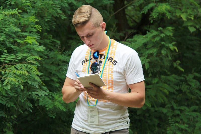 Brusilov, Ucraina - 17 luglio 2017: Un tipo di sport in una maglietta bianca sta registrando i risultati delle prove Giovane vett fotografia stock libera da diritti