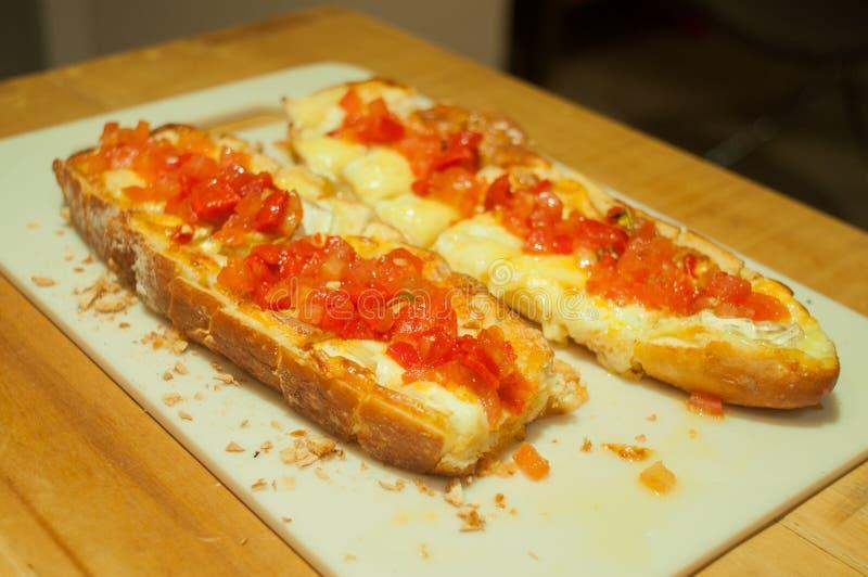 Brusqueta doble con los tomates y el queso italianos, en la tabla, ?ngulo de 45 grados imágenes de archivo libres de regalías