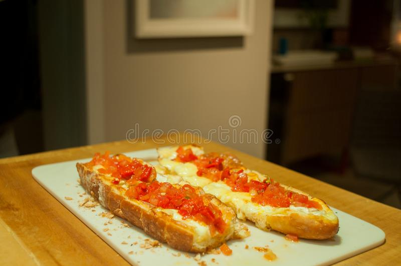 Brusqueta doble con los tomates y el queso italianos, en la tabla, de lejos foto de archivo